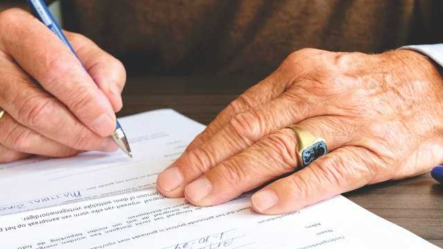 man signing bank will documents